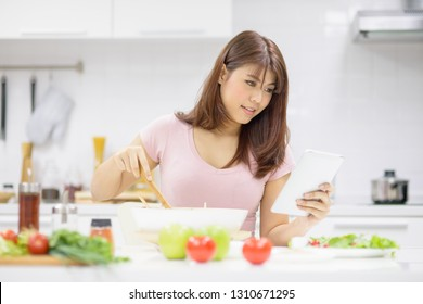 Beautiful young Asian woman cooking a healthy food by following cooking receipt  from online website using digital tablet in kitchen room.