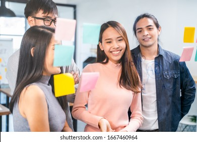 Beautiful Young Asian woman and creative team smiling and looking to glass wall with sticky notes in modern office. Business people teamwork, colleague coworker brainstorm. Asian business lifestyle