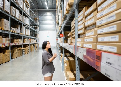 Beautiful young Asian woman customer or trainee staff work stocktaking with computer tablet at warehouse store, Asian working business woman concept