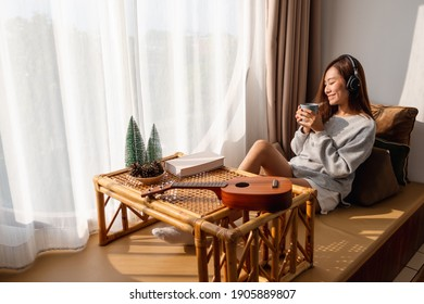 A beautiful young asian woman enjoy drinking coffee and listening to music with headphone at home, happiness and relaxation concepts