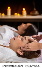 Beautiful young Asian woman enjoy head massage in tranquil spa salon, with candle.