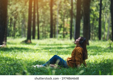 A beautiful young asian woman enjoy listening to music with headphone with feeling happy and relaxed in the park