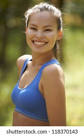 Beautiful young Asian woman exercising in rural scene with autumn colors in background