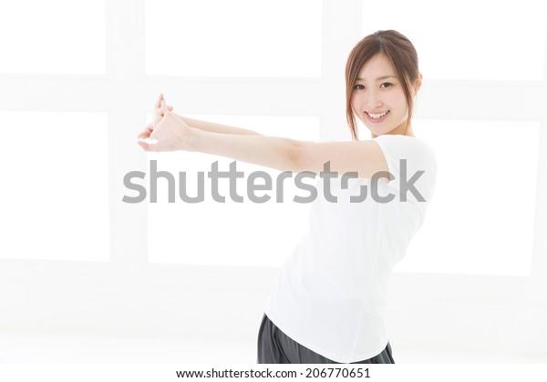 部屋で運動する美しいアジアの若い女性