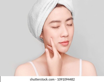 Beautiful young asian woman  face with a towel on her head put hand on cheek relaxed Spa and Beauty , her eyes closed against grey background