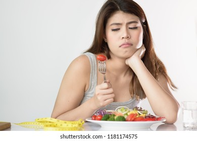 Beautiful young Asian woman feeling boring while eating fresh vegetable. Woman do not want to eat vegetables because of taste of vegetable or dislike dieting.