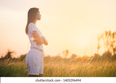Beautiful young asian woman in a field with sunlight