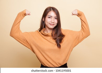 Beautiful young Asian woman flex bicep on beige background