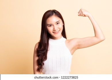 Beautiful young Asian woman flex bicep   on beige background.