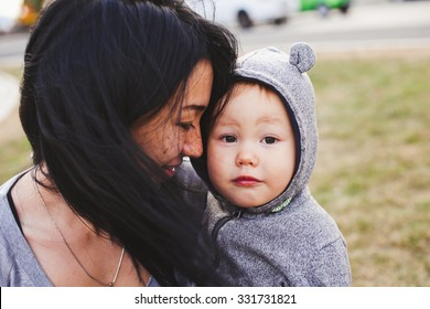 Beautiful young asian woman with freckles and her son outdoors. Mother brunette with dark hair holds her blond son in bear hood. Emotions on baby face. Unusual appearance, diversity, heredity concept