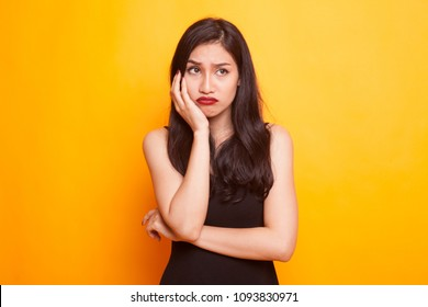 Beautiful young Asian woman get bored on yellow background