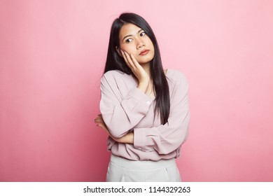 Beautiful young Asian woman get bored on pink background
