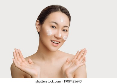 Beautiful young Asian woman gets cream in her face. The concept of skin care and hydration. a young woman with perfect clean skin health.