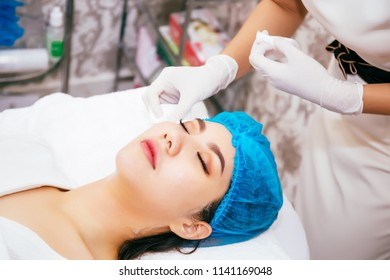 Beautiful young Asian woman getting her face cleansed by beautician at cosmetology beauty clinic