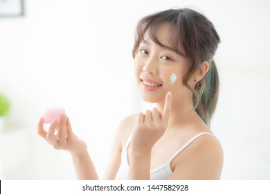 beautiful young asian woman happy applying cream or lotion with moisturizer to skin face, beauty asia girl applying skincare touch facial with cosmetic makeup, healthy and wellness concept.