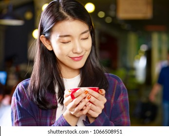 beautiful young asian woman holding a cup of coffee smiling with eyes closed.