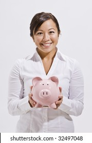 A beautiful and young asian woman holding a piggy bank.  She is smiling at the camera. Vertically framed shot.