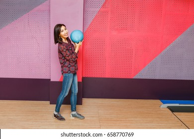 Beautiful young asian woman holding bowling ball and looking at the camera.