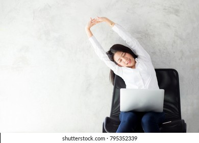 Beautiful young asian woman with laptop stretch and exercise relax after work success, modern office with copy space, freelance business concept.