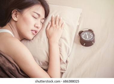 Beautiful young asian woman laying on bed indoors with alarm clock.