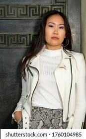 A beautiful young asian woman is leaning on an old door.