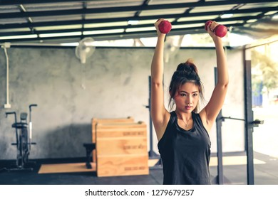 Beautiful young asian woman lifting dumbbell at gym.