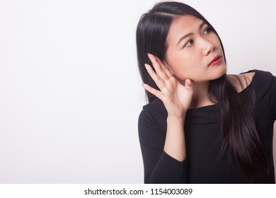 Beautiful young Asian woman listen to something on white background