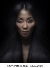 Beautiful young asian woman with long hair on dark background