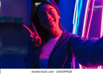 Beautiful young asian woman with long dark hair standing infront of a neon wall
