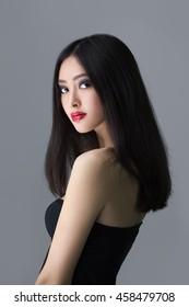 Beautiful young asian woman with long hair on dark gray isolated background