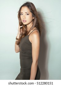 beautiful young asian woman with long hair posing in casual clothes and wearing a wrist watch