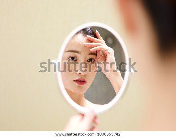 beautiful young asian woman looking at self in mirror, hand on forehead.
