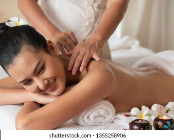 Beautiful young asian woman lying smile on the bed Getting a Salt Scrub Beauty Treatment in the Health Spa. Body Scrub. Select focus face women