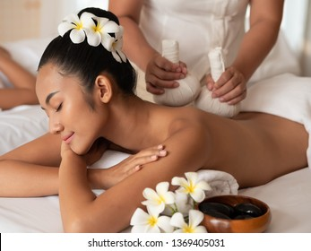 Beautiful young asian woman lying on the bed having a massage with herbal compresses in a spa. Thai massage for health. Select focus face women