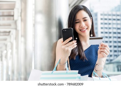 Beautiful young Asian woman making payment digitally with credit card after shopping online using mobile phone application technology