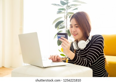 Beautiful young Asian woman ordering and buying music store on internet with laptop and holding credit card on hand in the room at home or condo, Happy buyer, payment and shopping online concept