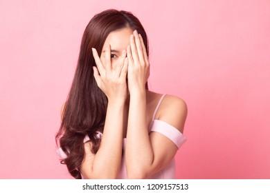 Beautiful young Asian woman peeking through fingers on pink background