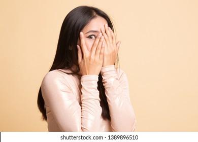 Beautiful young Asian woman peeking through fingers on  beige background