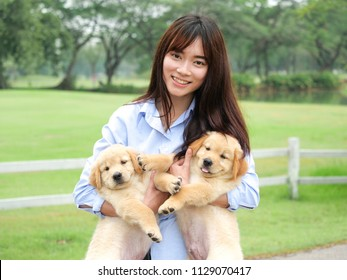 Beautiful young asian woman playing with a cute golden retriever dog in the park.