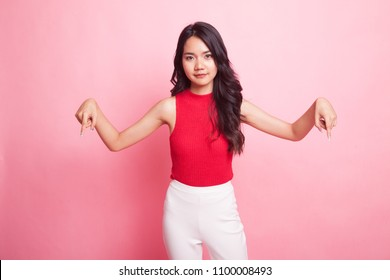 Beautiful young Asian woman point down to blank space on pink background