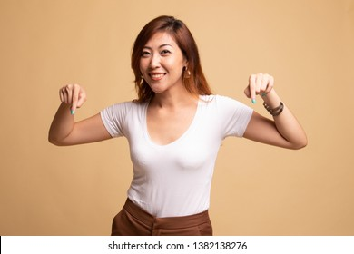 Beautiful young Asian woman point down to blank space on beige background