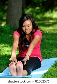 Beautiful young Asian woman practicing yoga in a park setting (forest clearing) on a blue mat. Here she makes a funny face while trying to stretch her hamstrings and back by touching her toes