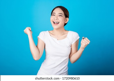 Beautiful young asian woman pretending to be happy with big smile happy beaming face in seamless blue  isolated background. Presenter promotion, happy lifestyle, fresh pretty girl concept.