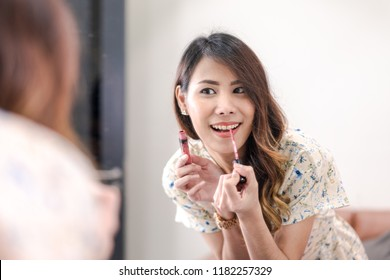 Beautiful young Asian woman professional beauty blogger applying makeup, charming girl look at mirror, use lip brush for lipstick dyes her lips lipstick pink, doing a make up tutorial. Selective focus