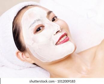 beautiful young asian woman receiving a facial skincare treatment.