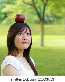 Beautiful young Asian woman with red apple on her head.