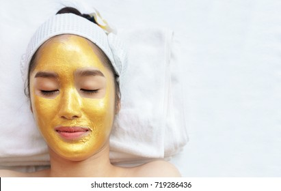 Beautiful young Asian woman relaxing , lying on massage table and having high quality and authentic pure gold facial mask for spa treatment to keep her skin glowing, hydrated, and radiant