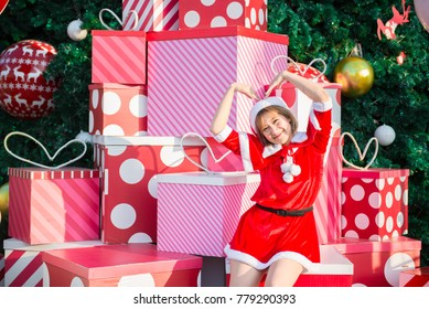 Beautiful young asian woman in Santa Claus clothes outdoors,Thailand people,Sent happiness for children,Merry christmas,Welcome to winter,Decorated christmas background