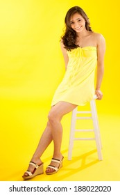 Beautiful young Asian woman seated on stool. She is wearing a yellow sun dress coordinated with the yellow background. Studio shot.