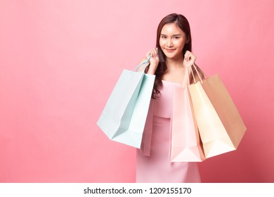 Beautiful young Asian woman with shopping bags on pink background